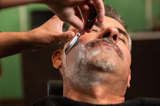 homme entrain de se faire raser la barbe